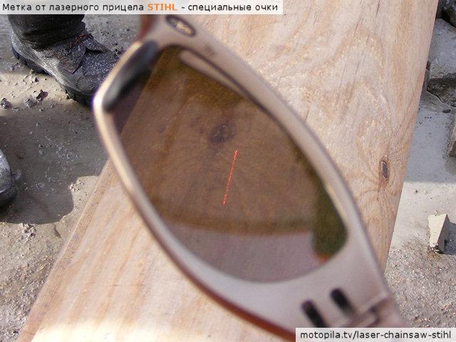 Метка от лазерного прицела Stihl в солнечную погоду на оцилиндрованном бревне. Вид через специальные очки.