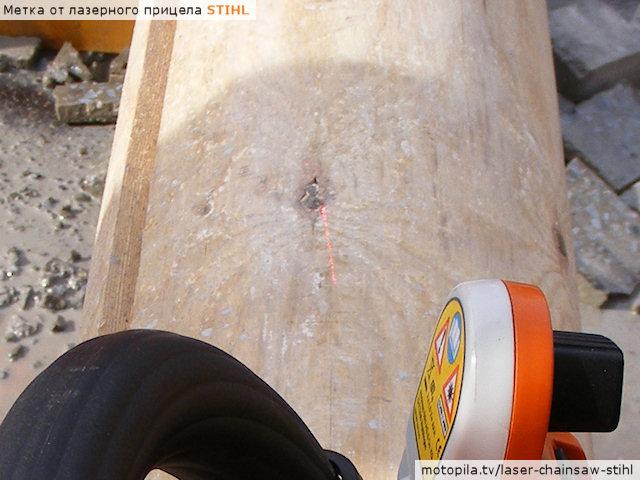 Метка от лазерного прицела Stihl в солнечную погоду на оцилиндрованном бревне